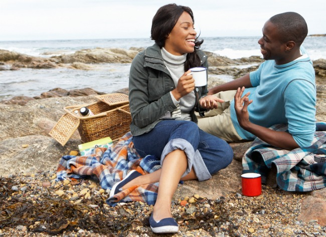 happy-black-couple-having-picnic-on-rocks-near-beach-smaller